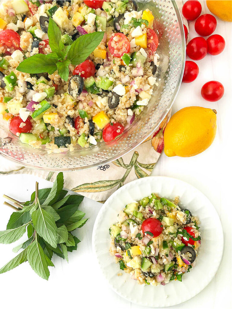 bowl and white plate with vegetable quinoa salad and fresh mint sprig and lemons