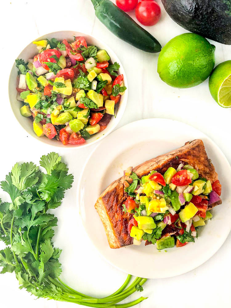 white plate with salmon and a bowl with avocado tomato salsa, cilantro and limes