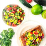 a piece of salmon topped with chunky avocado salsa and text
