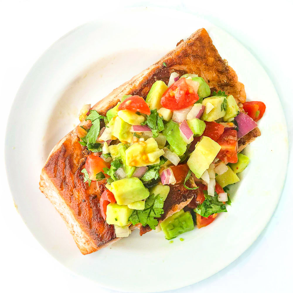 white plate with salmon topped with chunky avocado salsa