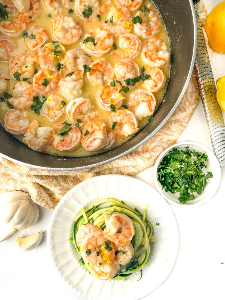 pan and plate with garlic butter shrimp and zucchini noodles with parsley and garlic