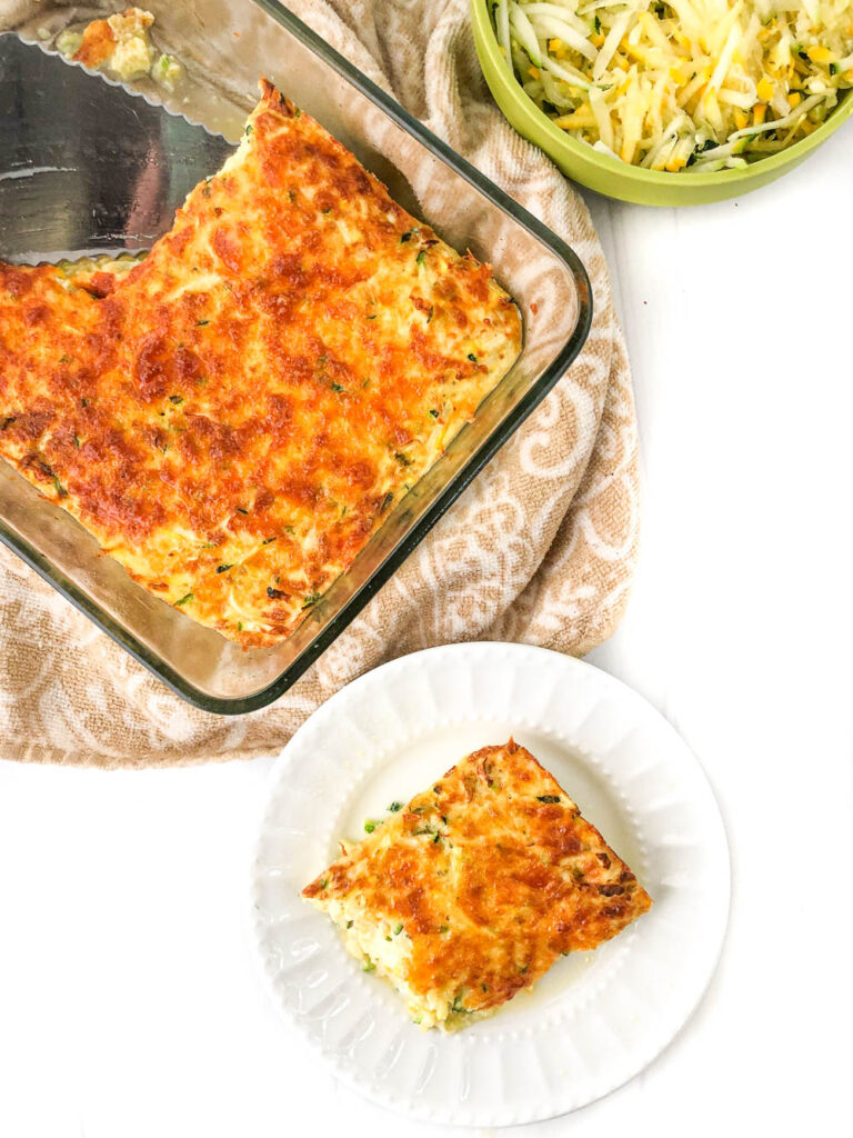 baking dish and white plate with some keto zucchini egg casserole and a bowl of shredded squash