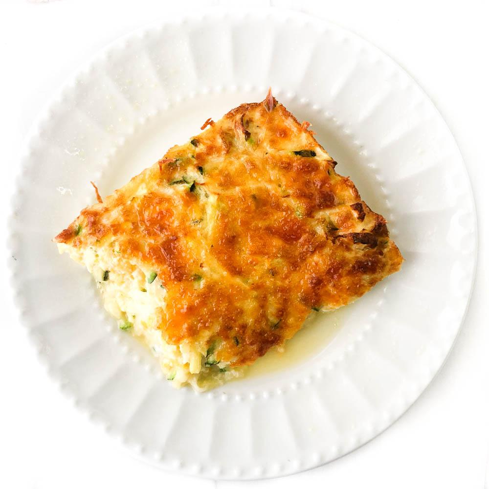 white plate with a slice of keto zucchini and squash casserole