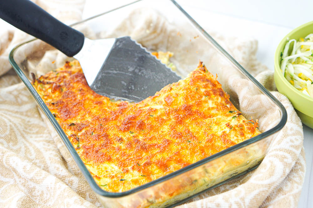 glass baking dish with keto cheesy casserole with a piece take out