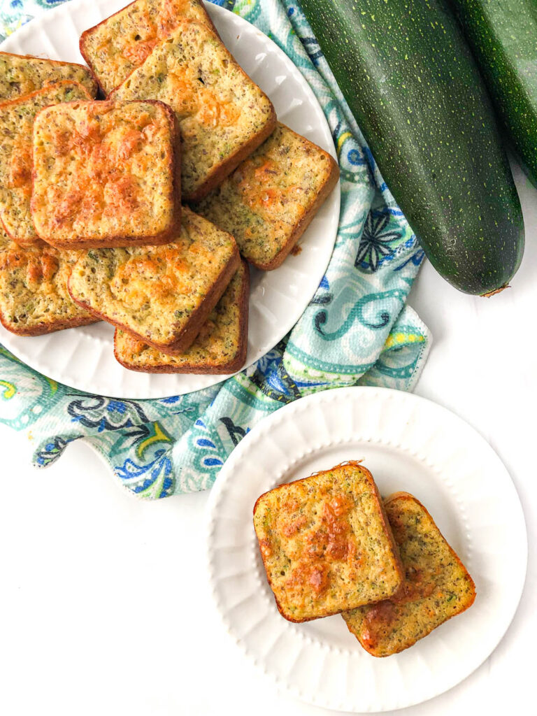 overhead view fo two white plates with the low carb zucchini square muffins and fresh zucchini
