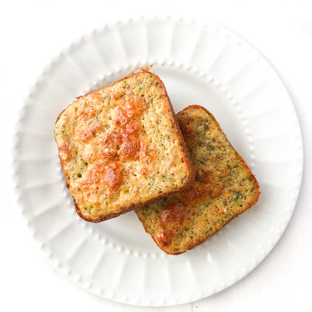 white plate with 2 zucchini protein powder muffins