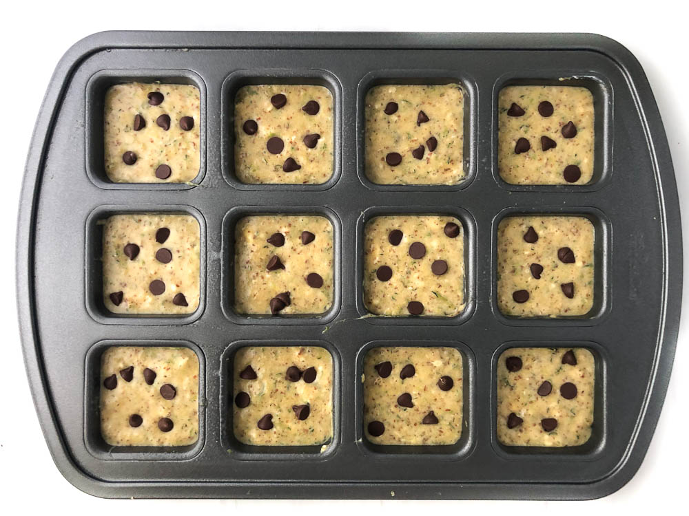 muffin tin with raw protein powder muffins and chocolate chips