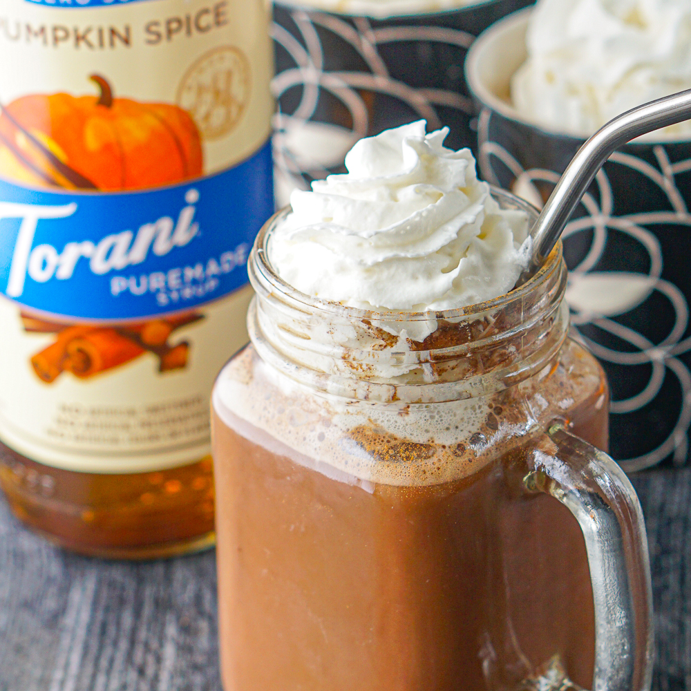 closeup of a glass jar cup with hot chocolate with whipped cream and silver straw