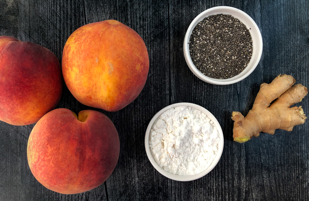 3 peaches and a bowl of chia seeds and a bowl of powder sweetener and ginger root
