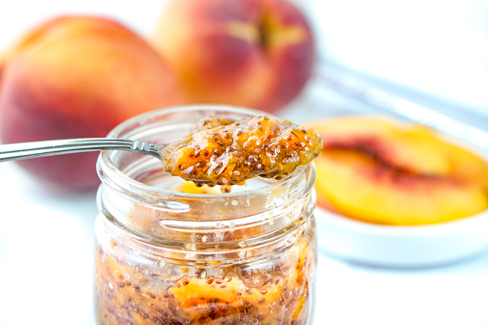 closeup of a jar of peach jam with a spoonful and fresh peaches in the background