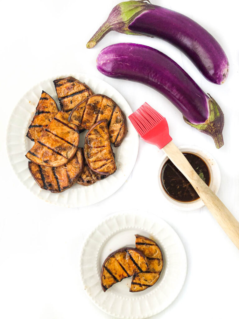 aerial view of white plates with grilled eggplant and some fresh purple ones alongside and a bowl of marinade