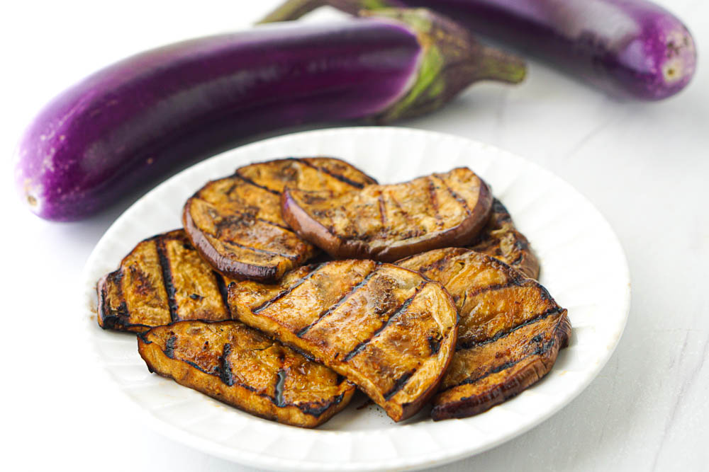 slices of eggplant on white plate after they are cooked on the grill