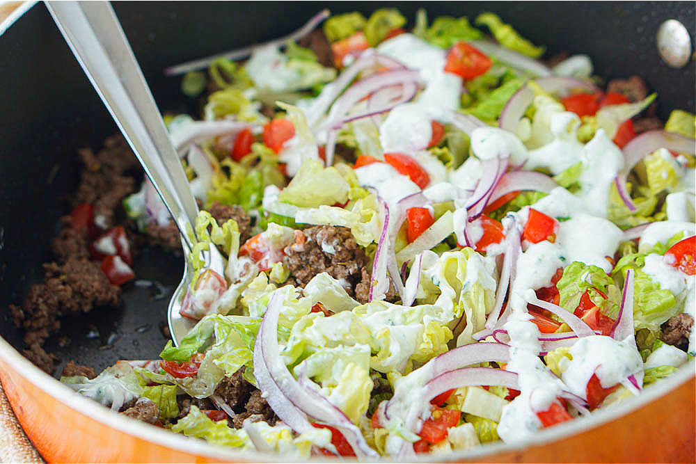 closeup of orange skillet with finished gyro ground beef dinner and spoon