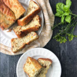 white plate with sun dried tomato protein bread and fresh herbs with text