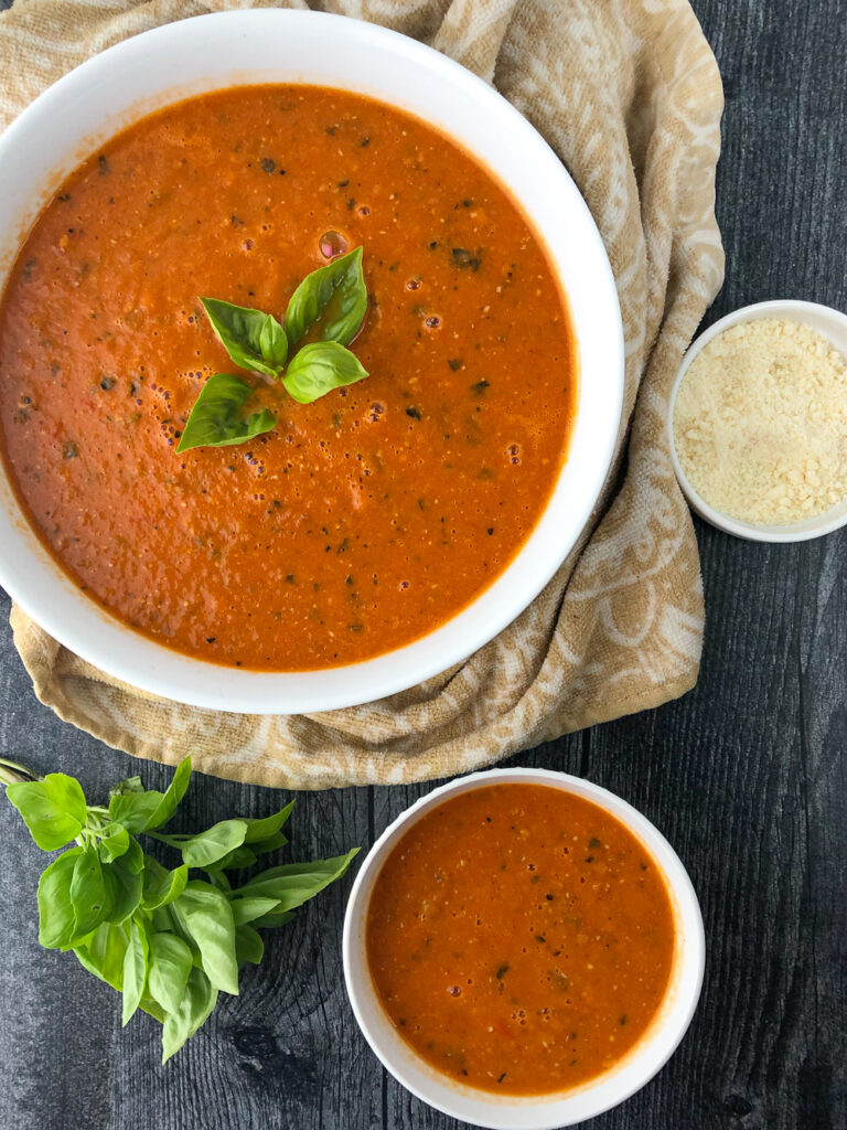 aerial view of bowls of roasted tomato soup with a bowl of parmesan cheese and fresh basil
