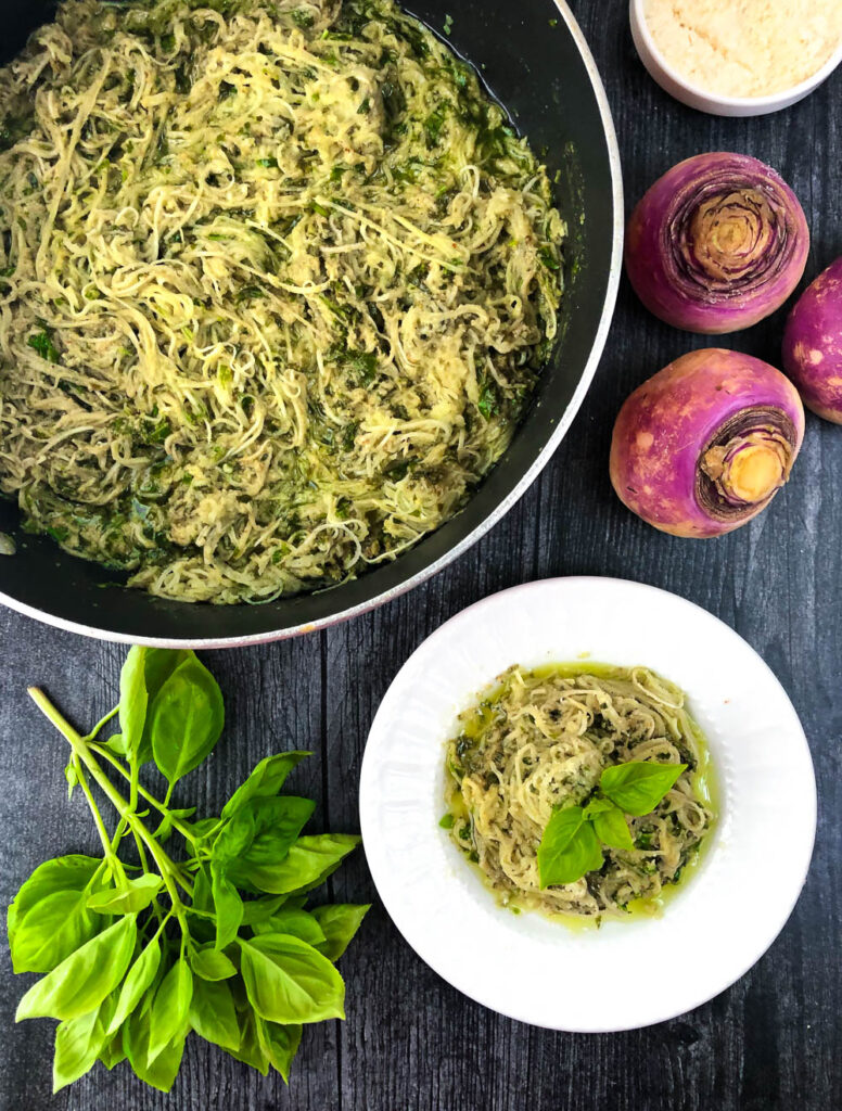 pan of gluten free pesto veggie noodles and raw turnips and sprigs of basil