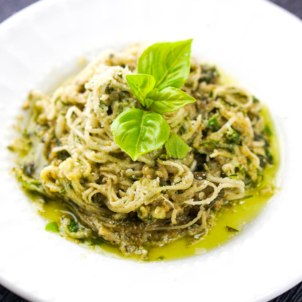 closeup of a white plate with turnip noodles mixed in basil pesto