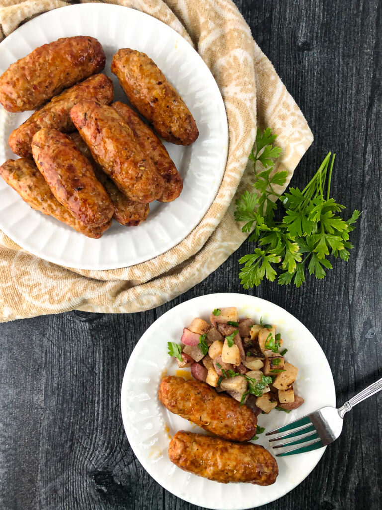 white plates with air fryer sausage and fresh parsley