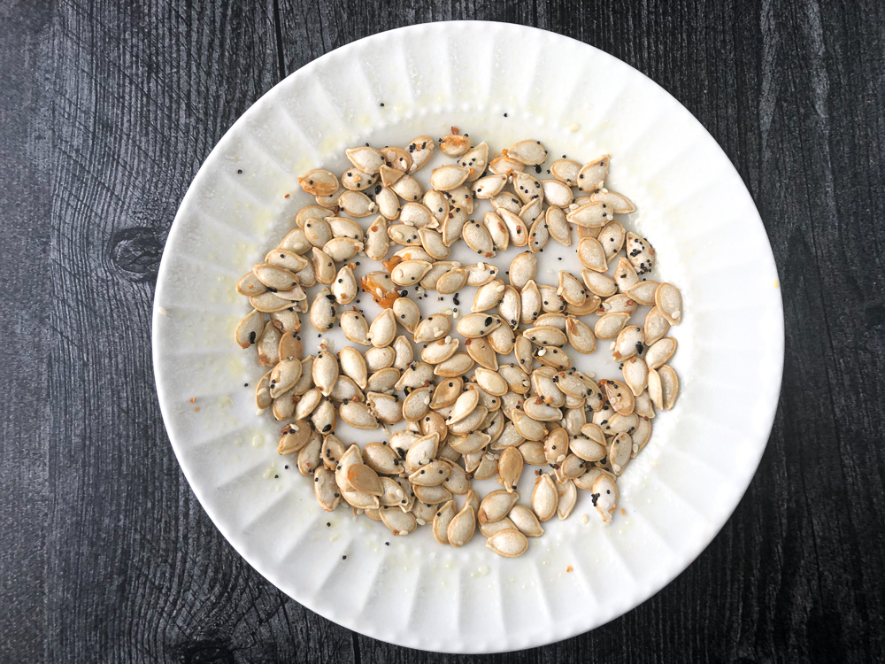 white plate with raw seeds with everything bagel spice