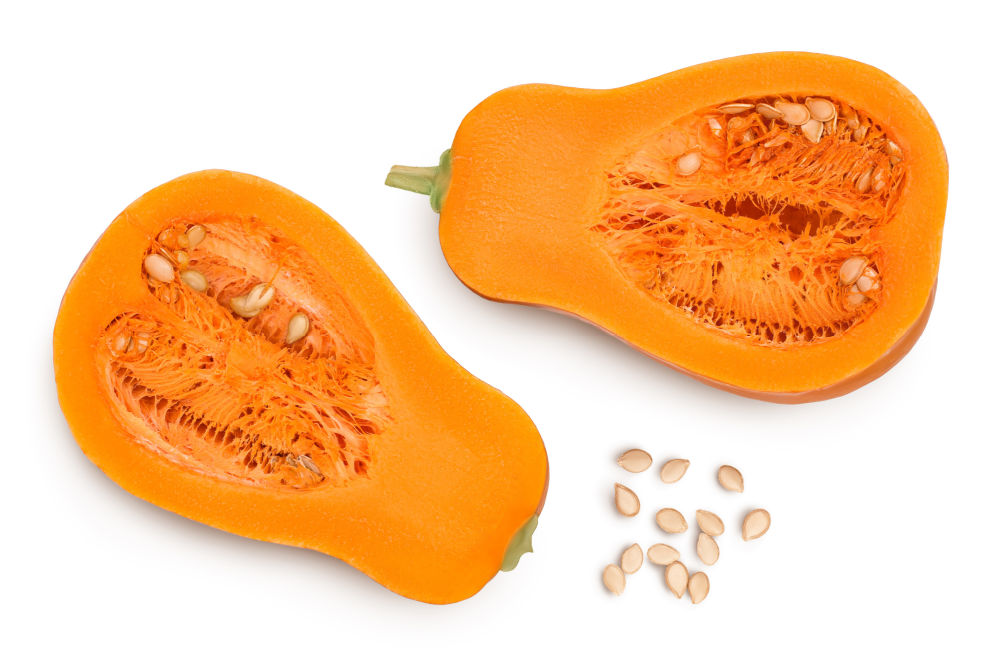 a butternut squash cut in half and scattered raw seeds