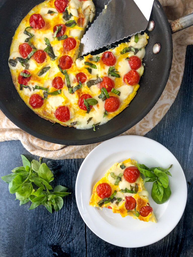 pan and plate with cheesy keto omelet with cherry tomatoes