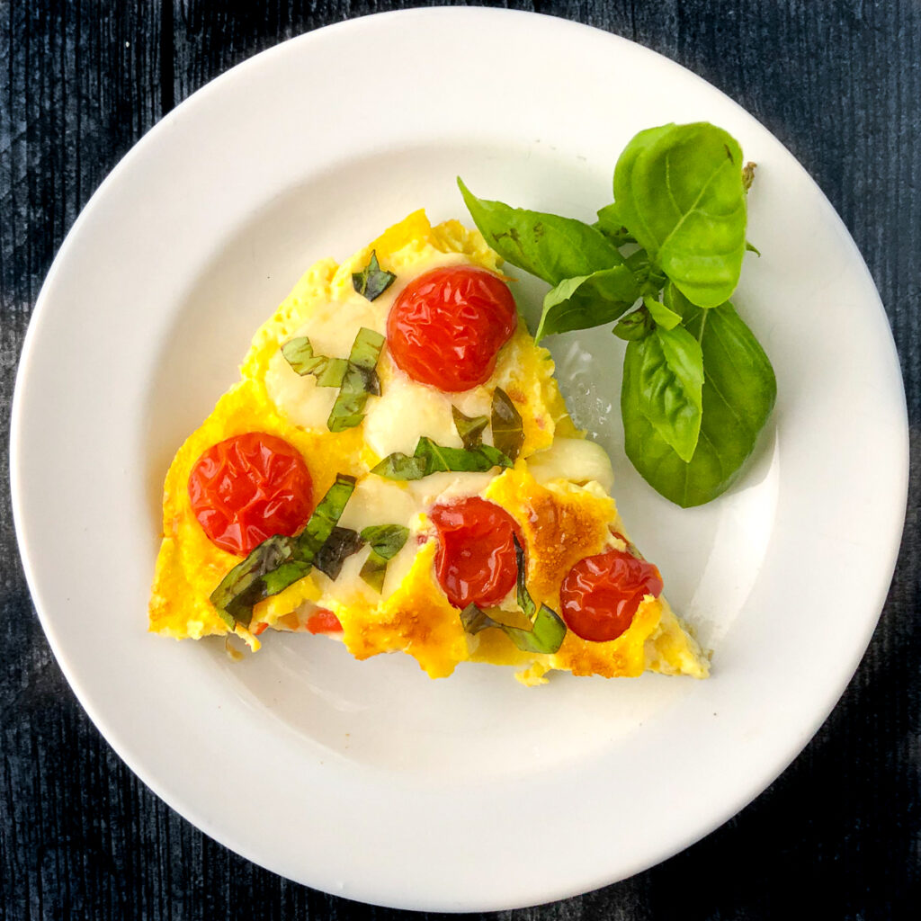 white plate with a slice of caprese omelet and sprig of fresh basil