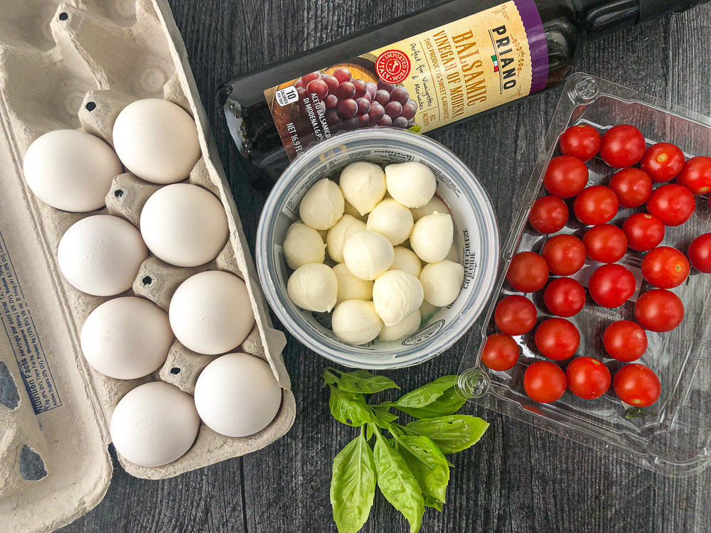 recipe ingredients - eggs, cherry tomatoes, fresh mozzarella, bottle of balsamic vinegar and fresh basil