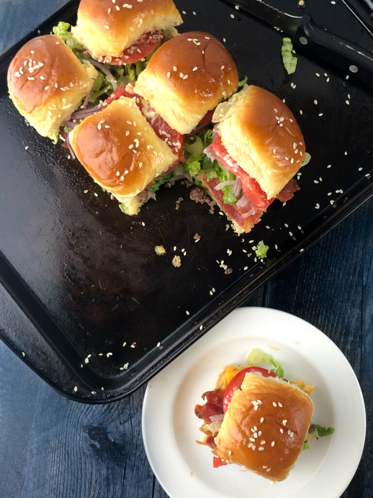aerial view of a baking tray and white plate with mini cheeseburgers