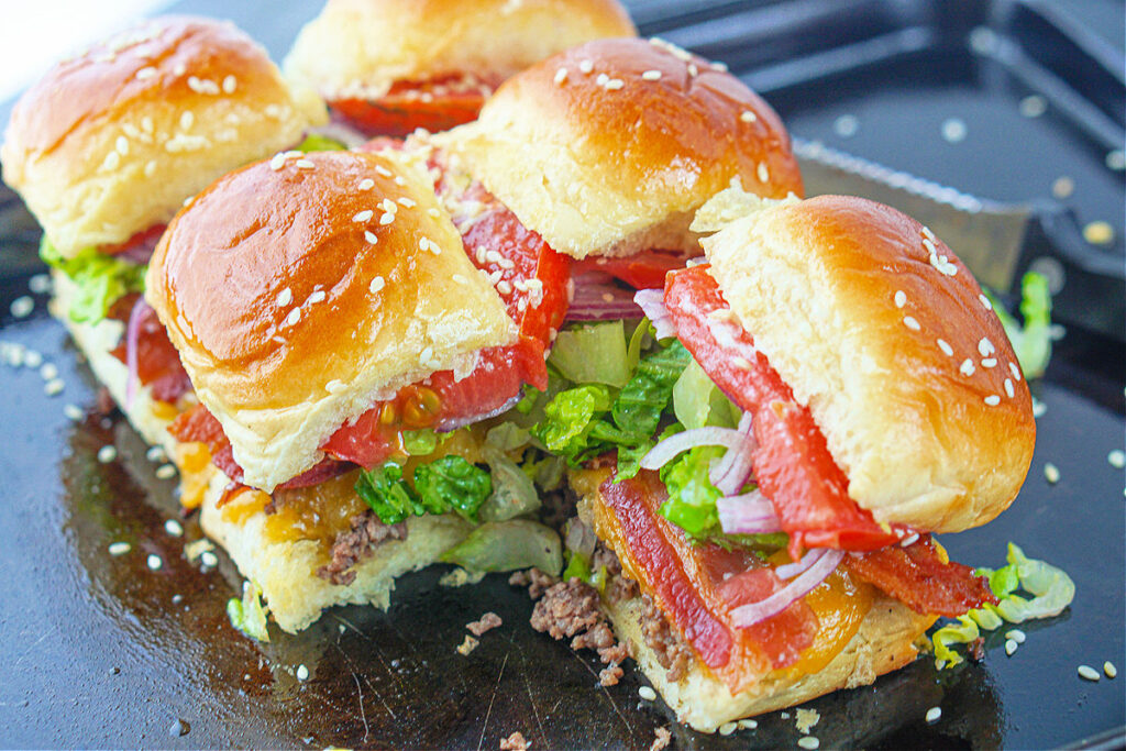 closeup of dinner rolls made into bacon cheeseburgers