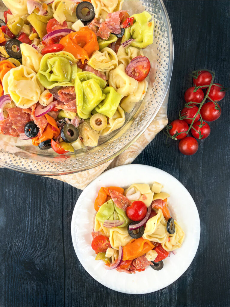 glass bowl and white plate with Italian pasta salad and fresh tomatoes