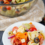 glass bowl with antipasto tortellini salad with text