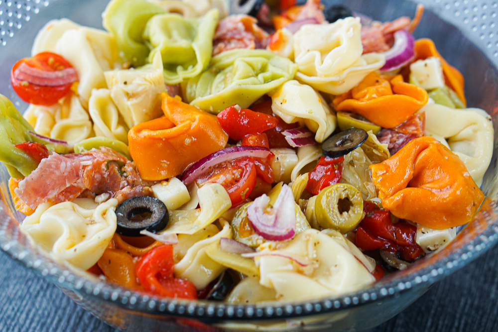closeup of bowl of antipasto tortellini salad with olives, cheeses, meats and more