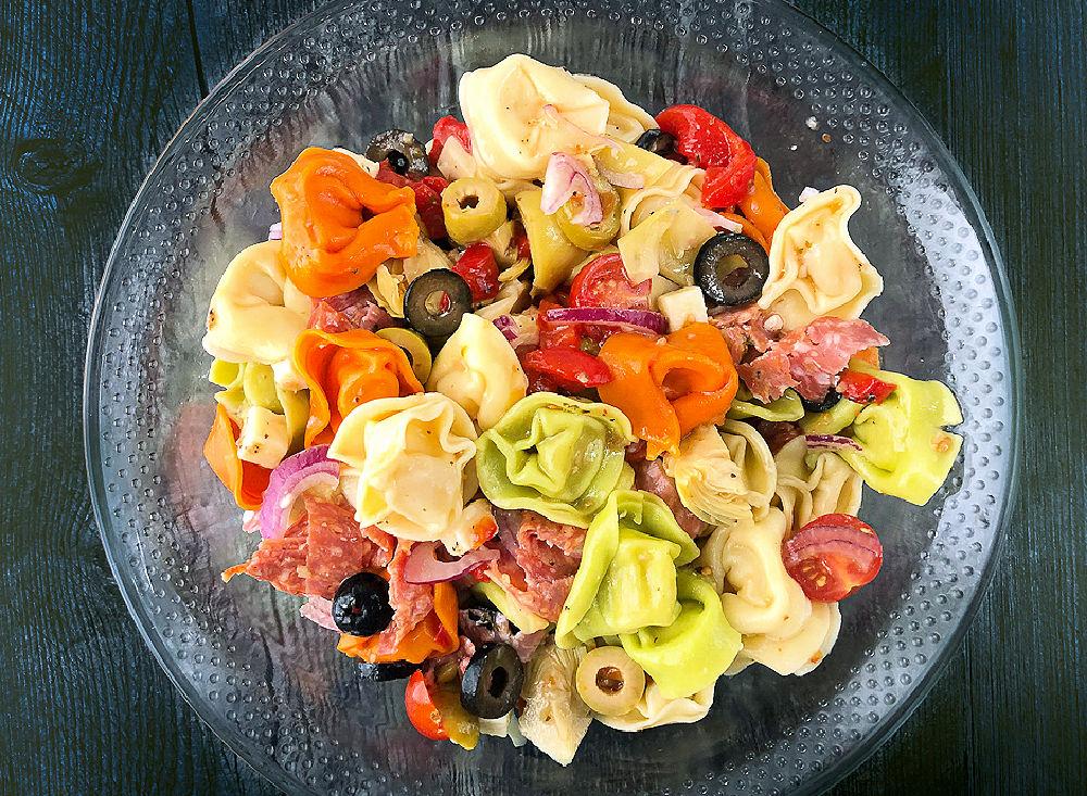 glass bowl of colorful tortellini pasta salad