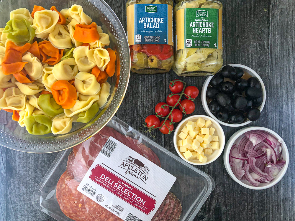 ingredients to make antipasto salad - tortellini, olives, jars of artichokes, tomatoes, onions, cheese and meats