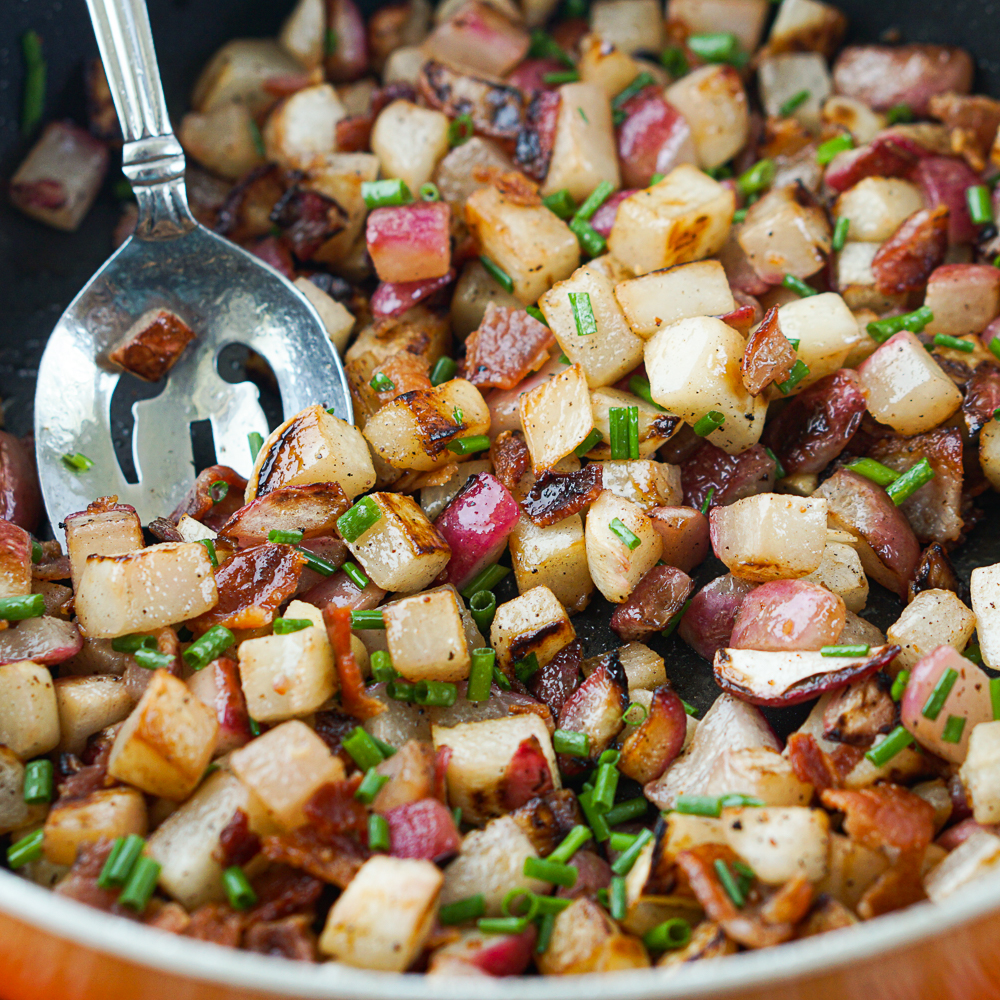 closeup of a pan of fried radishes and turnips with bacon