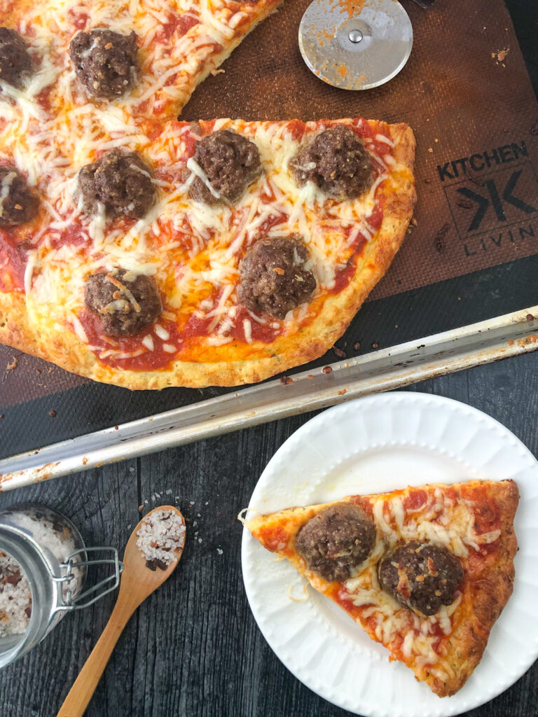 aerial view of a cookie sheet an plate with meatball gluten free pizza