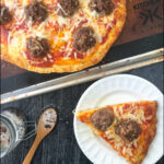 baking tray and white plate with keto meatball pizza and text