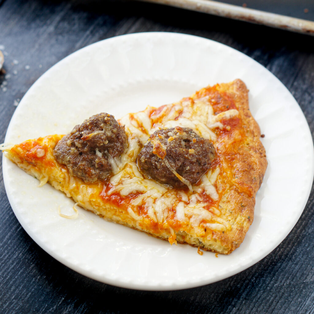 white plate with a slice of keto meatball pizza