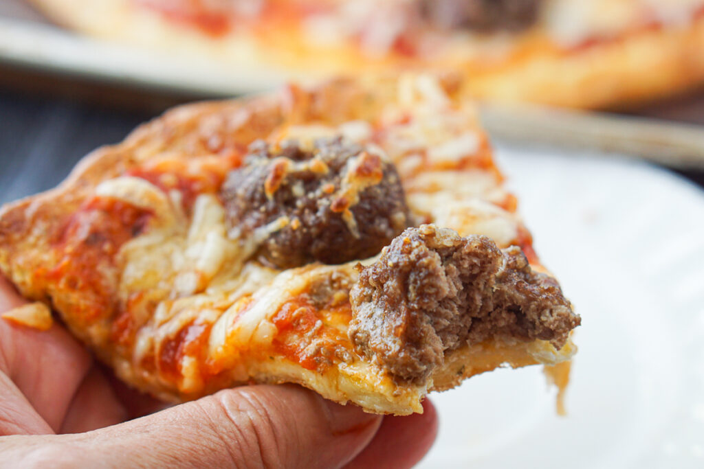 a hand holding a slice of the finished low carb pizza
